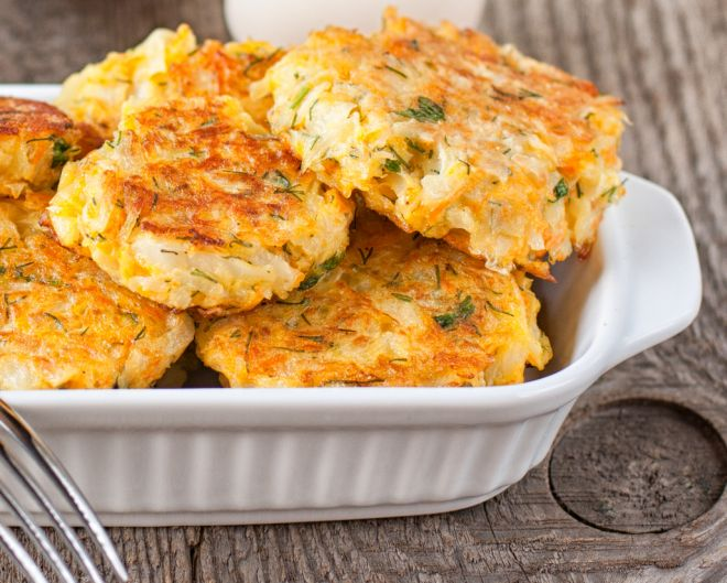 Healthy vegetarian cabbage patties with carrot and onion against the backdrop of sour cream sauce with herbs