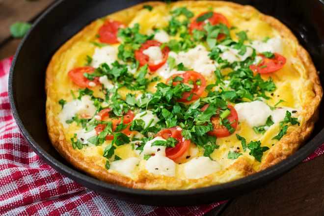 Omelet with tomatoes, parsley and feta cheese in pan